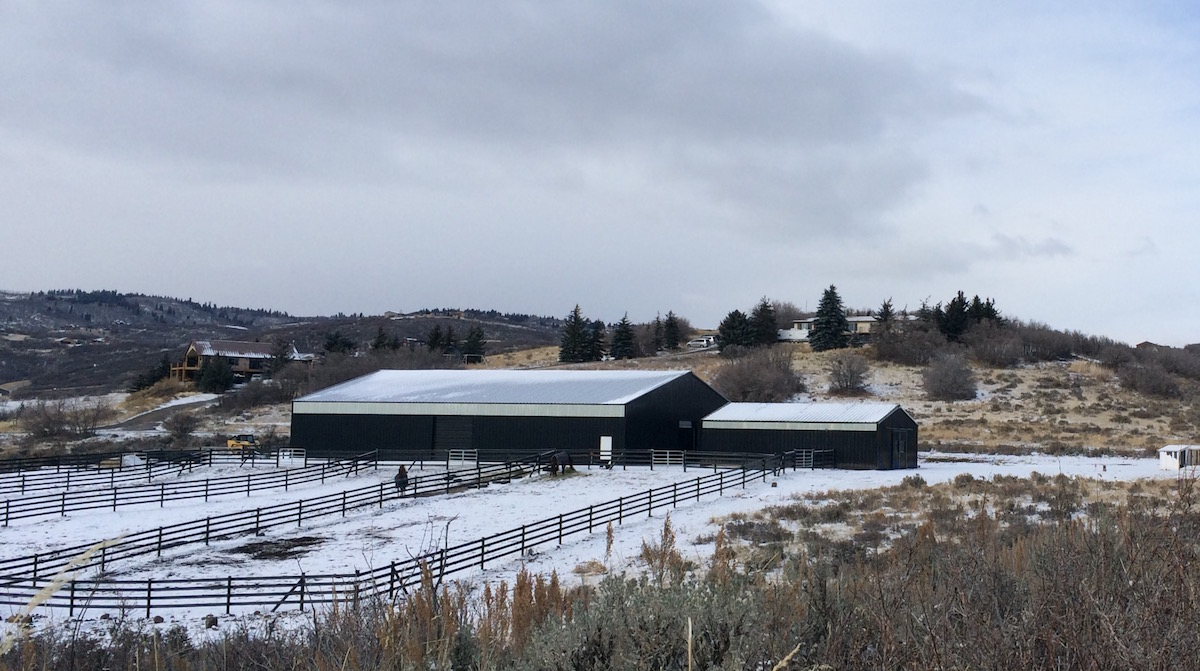Indoor steel building riding arena in the mountains, covered in snow
