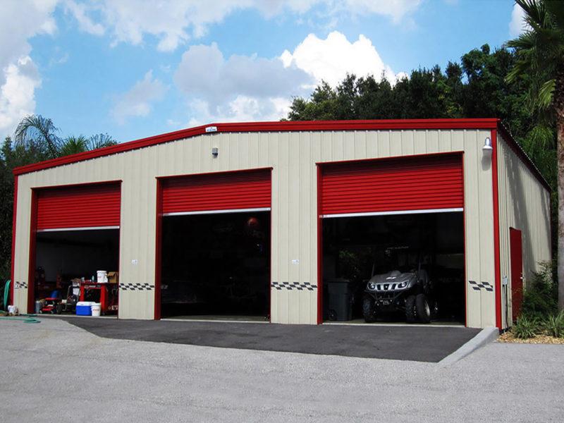 tan steel building garage with red trim, three garage doors