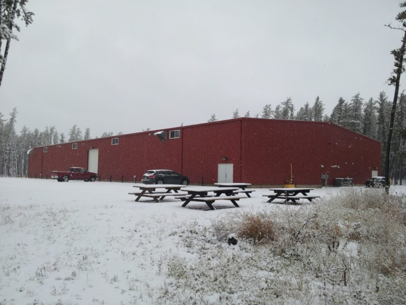 red Indoor steel building riding arena in the snow
