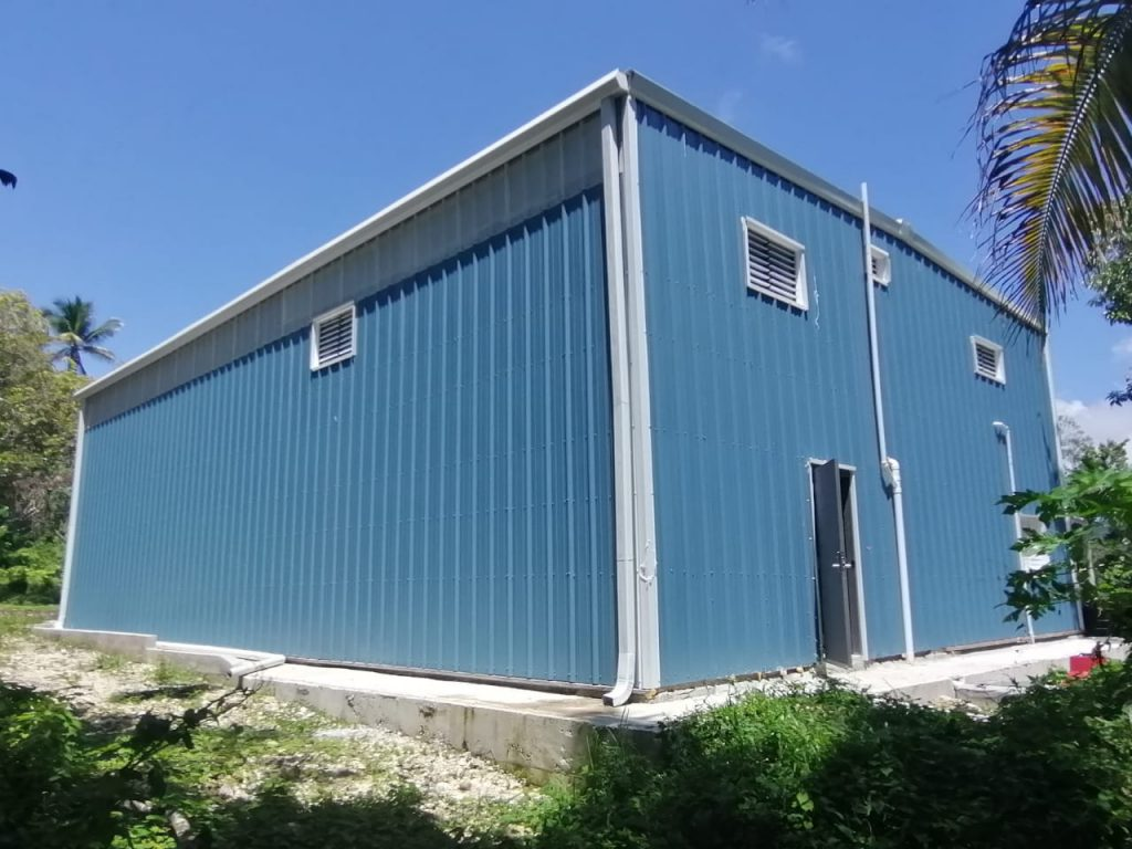 Cobalt blue office metal building with solar white gable trim, framed windows, gutter, downspouts and walk door