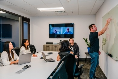 Allied Steel Buildings employes at the office and through video conference attending a meeting.