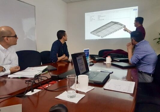 Allied Steel Buildings employees in the office holding presentations of client projects and concepts